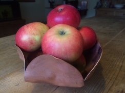 copper flower bowl filled with apples